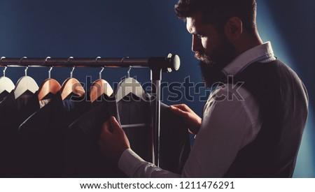 Tailor, tailoring. Men's suit, tailor in his workshop. Elegant man's suits hanging in a row. Luxury mens classic suits on rack in elegant men's boutique. #1211476291