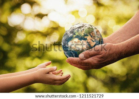 Close up of senior hands giving small planet earth to a child over defocused green background with copy space  Royalty-Free Stock Photo #1211521729