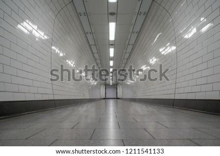 London, UK - October 2018: Empty London Underground white tiled corridor, tunnel #1211541133