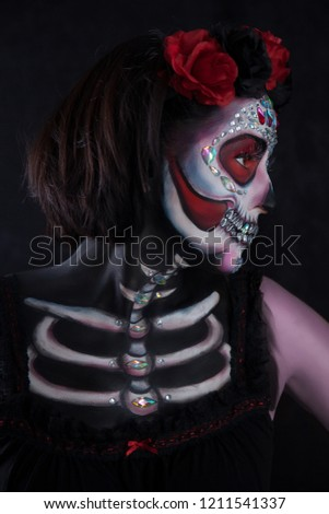 Beautiful women with skeleton face painting on black background.  Day of the Dead #1211541337