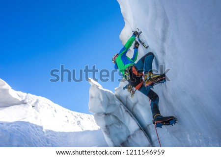 Epic shot of an ice climber climbing on a wall of ice. Mountaineer and climber on an adventure extreme ascent with ice axe and crampons. Alpine extreme climbing on a serac or creavasse. #1211546959