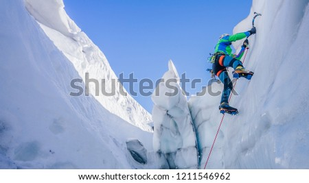 Epic shot of an ice climber climbing on a wall of ice. Mountaineer and climber on an adventure extreme ascent with ice axe and crampons. Alpine extreme climbing on a serac or creavasse. #1211546962