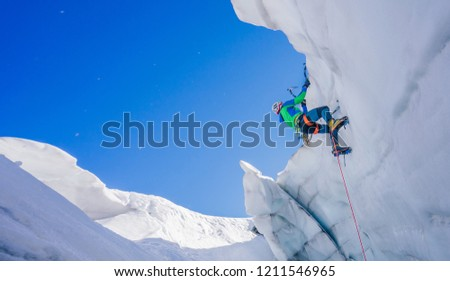 Epic shot of an ice climber climbing on a wall of ice. Mountaineer, climber or alpinist on an adventure extreme ascent with ice axe and crampons. Alpine extreme climbing on a serac or creavasse. #1211546965