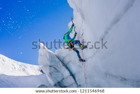 Epic shot of an ice climber climbing on a wall of ice. Mountaineer and climber on an adventure extreme ascent with ice axe and crampons. Alpine extreme climbing on a serac or creavasse. #1211546968