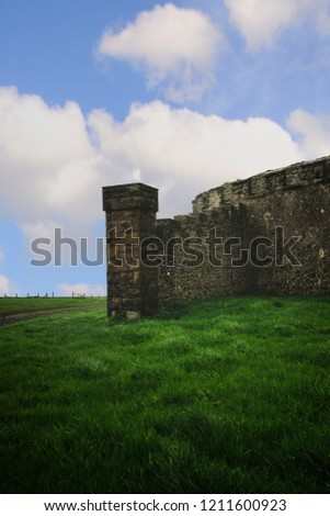 The exterior of ruins in Northern Ireland. A big sky with clouds fills the background and lush greenery in the foreground. #1211600923