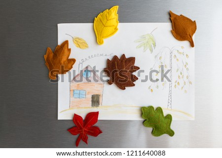 Colorful felt autumn leaves on refrigerator door. Children picture with house and tree hanging on fridge door. White kitchen on background. Diy fall autumn decoration for home