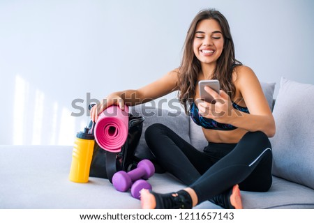 Happy fit woman counts calories and made post in blog after fitness workout. Healthy girl wearing sportwear hold smartphone in hand and considers calories in sport app aftrer training.
