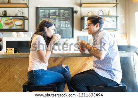 Side view of young man and woman having coffee while looking at each other at cafe counter #1211693494