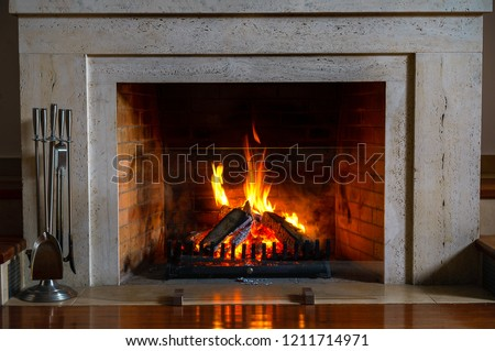 Wood burning in a cozy fireplace at home in interior. Fireplace as a piece of furniture. Christmas New Year concept decorations.