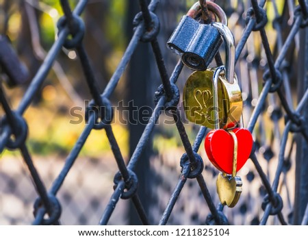 A group of four locks black gold and red color hangs on a wrought metal grid #1211825104