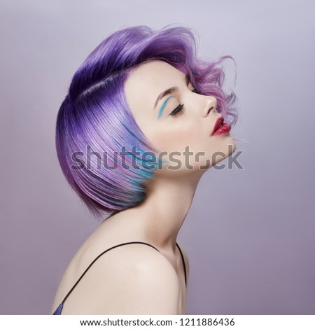 Portrait of a woman with bright colored flying hair, all shades of purple. Hair coloring, beautiful lips and makeup. Hair fluttering in the wind. Sexy girl with short  hair. Professional coloring #1211886436