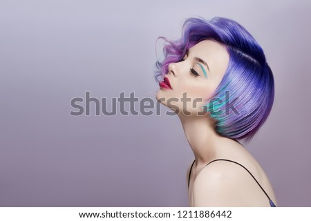Portrait of a woman with bright colored flying hair, all shades of purple. Hair coloring, beautiful lips and makeup. Hair fluttering in the wind. Sexy girl with short  hair. Professional coloring #1211886442