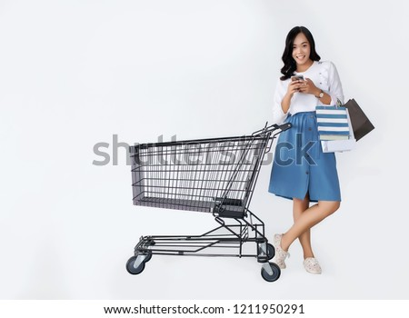 happy asian girl use mobile shopping with shopping cart and shopping paper bag #1211950291
