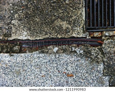 The black under ground cable in the cracked concrete. #1211990983