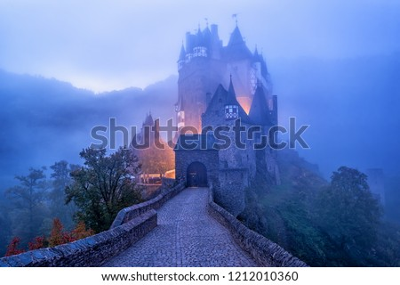 The medieval gothic Burg Eltz castle in the morning mist, Germany. Eltz Castle is one of the most impressive and famous castles in Germany. Royalty-Free Stock Photo #1212010360