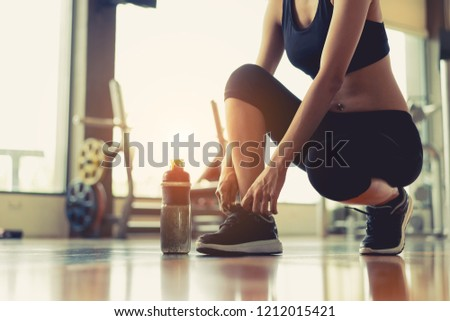 Woman sitting shoelaces with protein shake at fitness gym after running exercise workout for cardio and muscle building. #1212015421