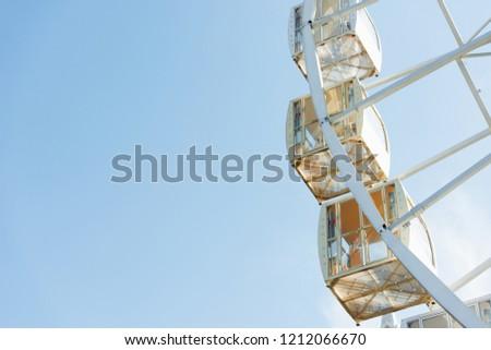 cabins of ferris wheel against blue sky in amusement park #1212066670
