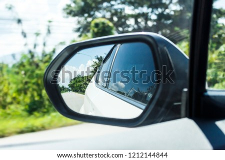 Close up of car mirror with reflection of behind the car. #1212144844