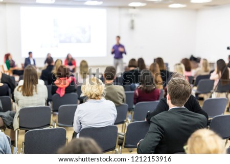 Speaker giving a talk in conference hall at business event. Audience at the conference hall. Business and Entrepreneurship concept. Focus on unrecognizable people in audience. #1212153916