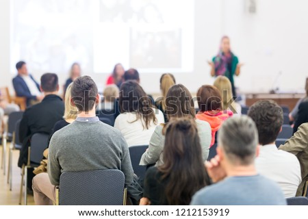 Female speaker giving presentation in lecture hall at university workshop. Audience in conference hall. Rear view of unrecognized participant in audience. Scientific conference event. #1212153919