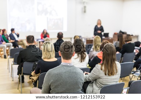 Business and entrepreneurship symposium. Female speaker giving a talk at business meeting. Audience in conference hall. Rear view of unrecognized participant in audience. Copy space on whitescreen. #1212153922