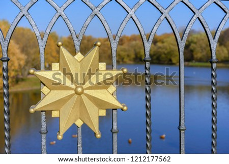 Golden decorative element at the forged fence. #1212177562