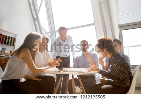 Cheerful diverse team people workers students laughing at funny joke while eating pizza together, friendly multi-ethnic colleagues group talking enjoying having fun and corporate lunch in office room #1212195505