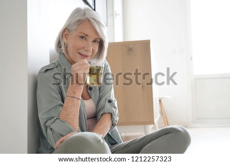 Attractive senior woman sitting on the floor at home with tea                              #1212257323