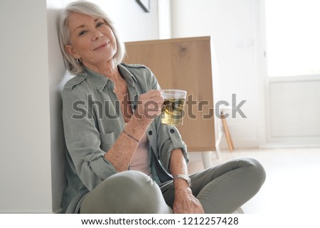 Attractive senior woman sitting on the floor at home with tea                              #1212257428