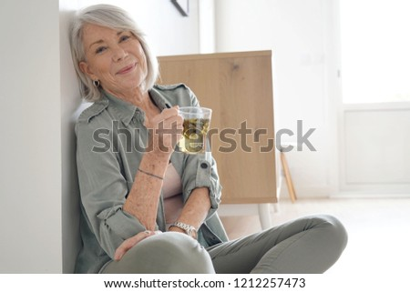 Attractive senior woman sitting on the floor at home with tea                              #1212257473