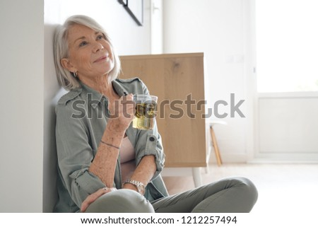 Attractive senior woman sitting on the floor at home                               #1212257494