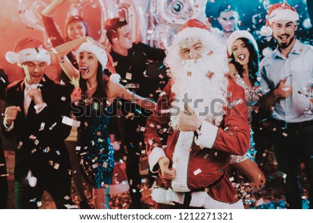 Man in Santa Claus Costume on New Year Party. Happy New Year. People Have Fun. Indoor Party. Celebrating of New Year. Young Women in Dresses. Young Men in Suits. Happy People. Man with White Beard. #1212271321