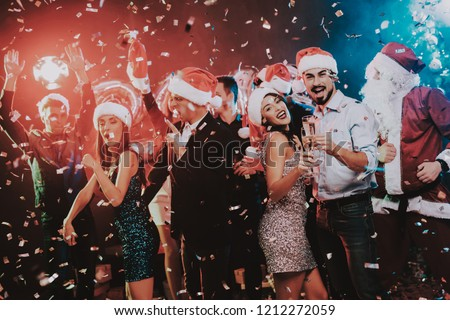 Happy Young People Dancing on New Year Party. Santa Claus. People in Red Caps. Happy New Year Concept. Glass of Champagne. Celebrating of New Year. Young Woman in Dress. Men in Suits. #1212272059