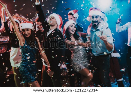 Happy Young People Dancing on New Year Party. Santa Claus. People in Red Caps. Happy New Year Concept. Glass of Champagne. Celebrating of New Year. Young Woman in Dress. Men in Suits. #1212272314