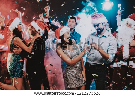 Happy Young People Dancing on New Year Party. Santa Claus. People in Red Caps. Happy New Year Concept. Glass of Champagne. Celebrating of New Year. Young Woman in Dress. Men in Suits. #1212273628