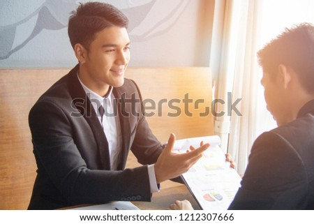 Two smiling positive businessmen discussing new project at meeting, joking and laughing, friendly nice manager consulting client, business partners having fun during discussion, good relationships Royalty-Free Stock Photo #1212307666