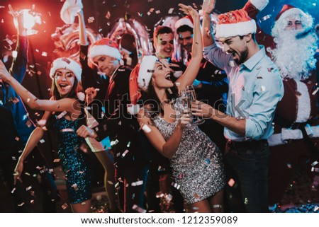 Happy Young People Dancing on New Year Party. Santa Claus. People in Red Caps. Happy New Year Concept. Glass of Champagne. Celebrating of New Year. Young Woman in Dress. Men in Suits. #1212359089