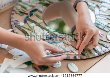 Workplace of the mosaic master: women's hands holding tool for mosaic details in the process of making a mosaic
