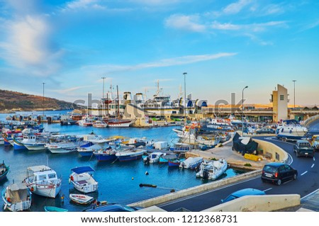 GHAJNSIELEM, MALTA - JUNE 15, 2018: The colorful fishing boats are moored at the shipyards in Mgarr Harbour, on June 15 in Ghajnsielem. #1212368731