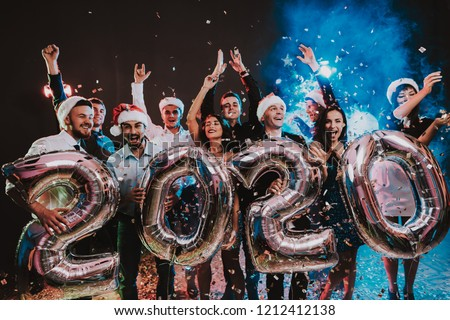 Smiling People with Baloons Celebrating New Year. Celebrating of New Year. Young Woman in Dress. Young Man in Suit. Santa Claus Cap. People with Gray Baloons. Happy New Year. People Have Fun. #1212412138