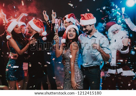 Happy Young People Dancing on New Year Party. Santa Claus. People in Red Caps. Happy New Year Concept. Glass of Champagne. Celebrating of New Year. Young Woman in Dress. Men in Suits. #1212415180