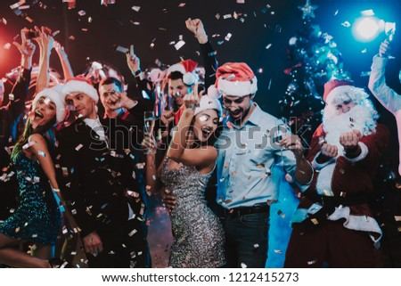Happy Young People Dancing on New Year Party. Santa Claus. People in Red Caps. Happy New Year Concept. Glass of Champagne. Celebrating of New Year. Young Woman in Dress. Men in Suits. #1212415273