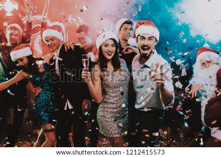 Happy Young People Dancing on New Year Party. Santa Claus. People in Red Caps. Happy New Year Concept. Glass of Champagne. Celebrating of New Year. Young Woman in Dress. Men in Suits. #1212415573