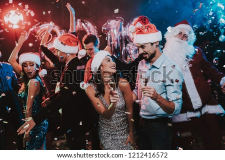 Happy Young People Dancing on New Year Party. Santa Claus. People in Red Caps. Happy New Year Concept. Glass of Champagne. Celebrating of New Year. Young Woman in Dress. Men in Suits. #1212416572