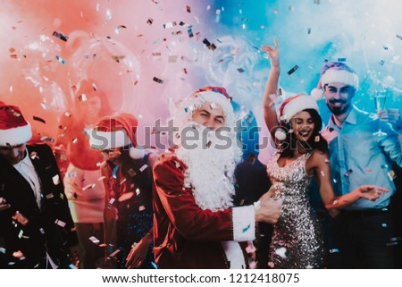 Man in Santa Claus Costume on New Year Party. Happy New Year. People Have Fun. Indoor Party. Celebrating of New Year. Young Women in Dresses. Young Men in Suits. Happy People. Man with White Beard. #1212418075