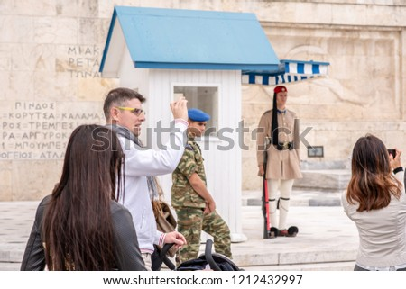 Athens, Greece / October 13, 2018: One man takes a photo with his phone, standing among a busy crowd of people gathered to see the soldiers at the famous Greek Parliament building near Syntagma Square #1212432997