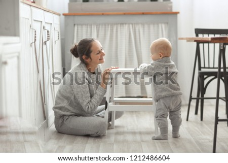 Beautiful young mother looks like the baby is standing at the stool, the real interior in the Scandinavian style. The concept of motherhood and safety. #1212486604