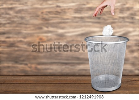Hand throwing out paper into trash basket #1212491908