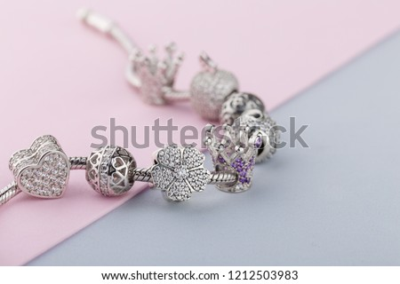 Bracelet with silver charm beads with gems. Flower, crown, ball, heart beads.  Product concept for jeweler Royalty-Free Stock Photo #1212503983