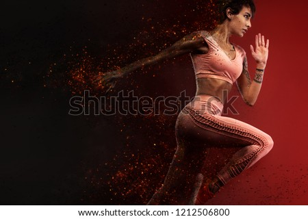 Fitness and sport motivation.. Strong and fit athletic, woman sprinter or runner, running on red background in the fire wearing sportswear. #1212506800
